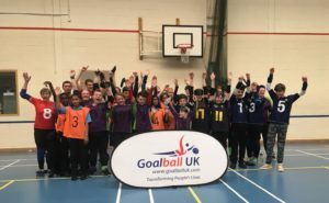 Group photo of players with arms in the air, cheering. Behind the Goalball UK banner
