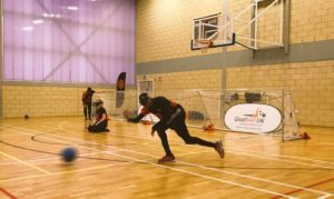 Action shot of goalball game, with player closest to camera taking a shot