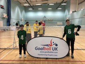 Young players smiling either side of the Goalball UK banner, with West Yorkshire Goalball Club in the background