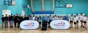 Group photo of children at a Goalball UK school competition, with GB player Caleb Nanevie in the centre