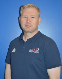 picture of Mark Winder in a blue polo shirt on a blue background