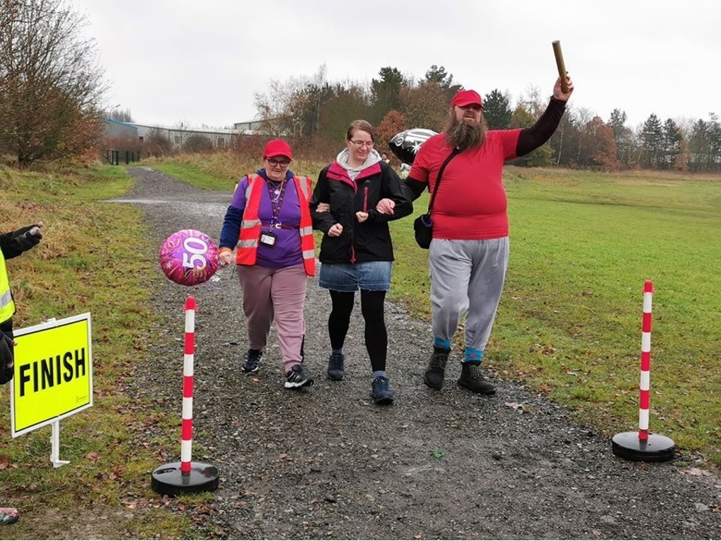 Chris Payne, holding aloft a 'golden baton' as he crosses the finish line at Poolsbrook parkrun together with Teresa (and a volunteer)