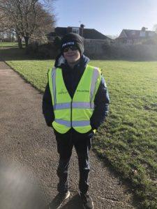 Bobbie-Jack from Winchester Goalball Club, wearing a hi-vis volunteer vest, ready to marshall at Basingstoke Junior parkrun