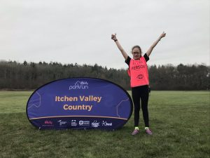 Keira from Winchester Goalball Club stood next to an 'Itchen Valley Country' parkrun banner