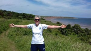 Kathryn smiling, with the cliffs of Filey (North Yorkshire) in the background