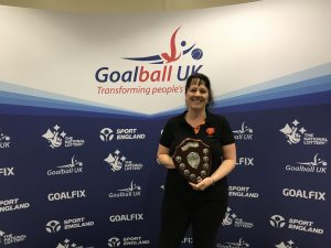Emma Evans receiving the Keith Lound Award in 2019, smiling and holding the award with a Goalball UK banner in the background.