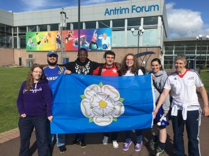 Group photo showing the Yorkshire based players in Northern Ireland, holding a flag of the Yorkshire Rose