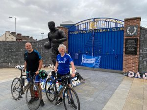 Phil and Kathryn stood, with their bikes, in front of a statue by the main gates at Goodison Park