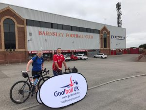 Kathryn and Phil, stood with their bikes, in front of a Goalball UK banner outside Oakwell Stadium
