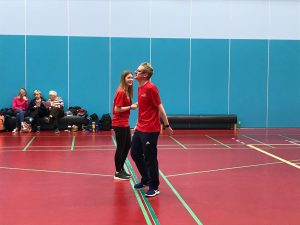 Imogen in the centre of the goalball court at the beginning of a game, shaking hands with her co-official