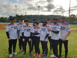 Team photo of the UK blind baseball team stood outside on a floodlit baseball diamond