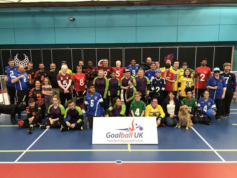 Group photo of the goalball family behind a Goalball UK banner
