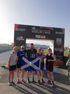 Paul with Scottish teammates proudly holding St. Andrews flag on the finish line of a triathlon