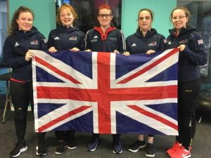 Image shows Megan stood with her GB teammates holding the Union Jack flag