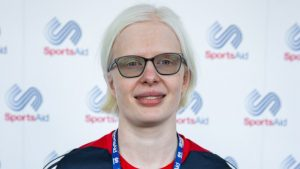 Image shows Sarah Leiter smiling in from of a SportsAid advertising board