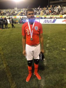 Image shows Rainbow stood on the pitch after representing England with an IBSA Blind Football World Grand Prix silver medal around his neck.