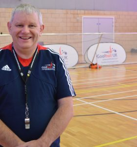 Smiley photo of Robert Avery in front of a goalball goal at The Factory Community Centre, Birmingham