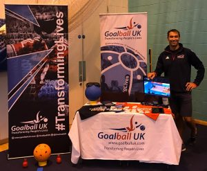 View of a standard Goalball UK stand at a university volunteering fair, with Steve Cox standing and smiling at the side.