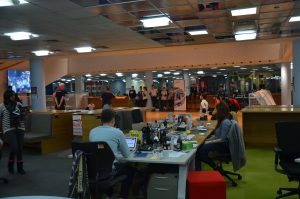 Corporate event in progress. Bermused employees looking on from their desk watching a goalball game.