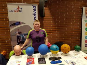 Sally and Tom Britton stood together in Croysutt Warriors kit. Tom is crouched down resting his head on top of some tape!