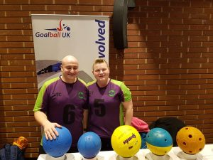 Sally and Tom Britton stood together at a stand promoting goalball.