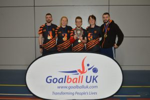 Dom Roper in a group Fen Tigers photo in front of a Goalball UK banner.