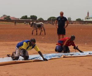 Chris Davies coaching goalball in a dusty field in Ghana. Meanwhile a cow is walking behind the court!