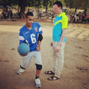 Sal Gamil from Birmingham Goalball Club demonstrating a goalball throwing technique to a participant in Ghana.
