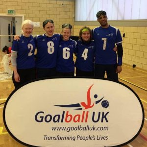 Warren and the rest of the Cambridge team stood together in front of a Goalball UK banner.