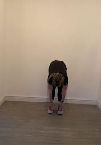 Image shows Megan in the starting position for the explodig star jump, bent over touching her toes
