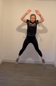 Image shows Megan mid-jump with her arms and legs out in a start position