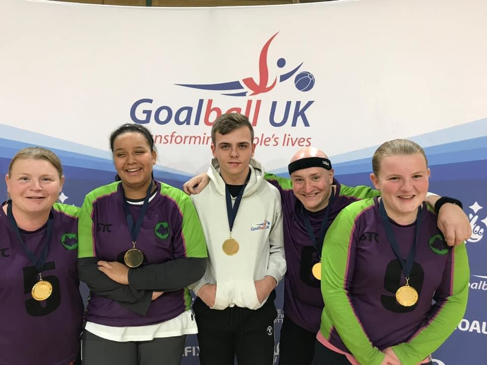 Image shows Alex stood with members of the Croysutt Warriors team in front of a Goalball UK banner. She has a big smile on her face!