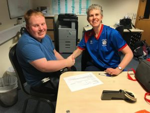 Image shows Ben signing for South Yorkshire Goalball Club. He is pictured shaking hands with Kathryn Fielding following him signing for the club.