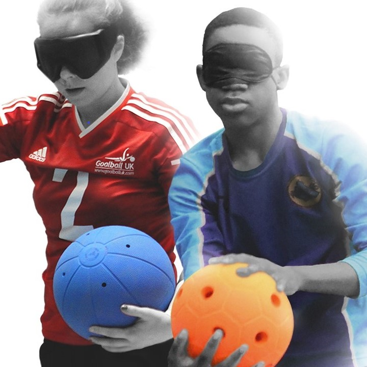 A Great Britain women's player holding a goalball, stood next to a young male player preparing to shoot an orange jingle ball.