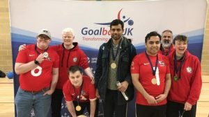 Image shows Joe Scott stood with his London Elephants teammates after a tournament in front of a Goalball UK banner. They are all showing off their medals!