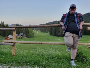 Image shows Joe Scott leaning against a wooden fence with a beautiful Slovenian landscape behind him