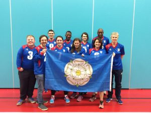Images shows Ben with his South Yorkshire team. All are stood smiling holding a Yorkshire flag.
