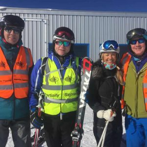 4 skiers wearing hi-vis partially sighted vests ly impi