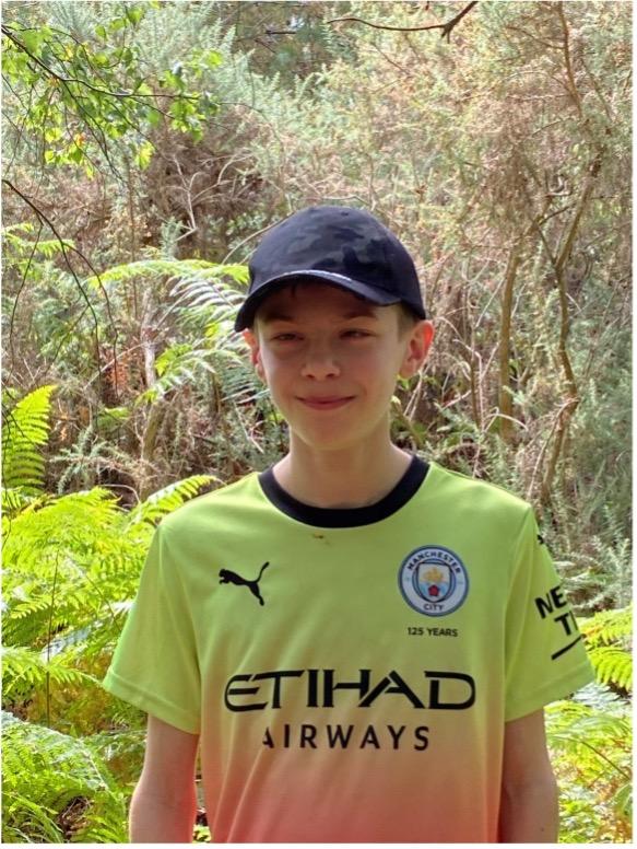 Image shows Bobbie-Jack stood smiling at the camera wearing his Manchester City football shirt