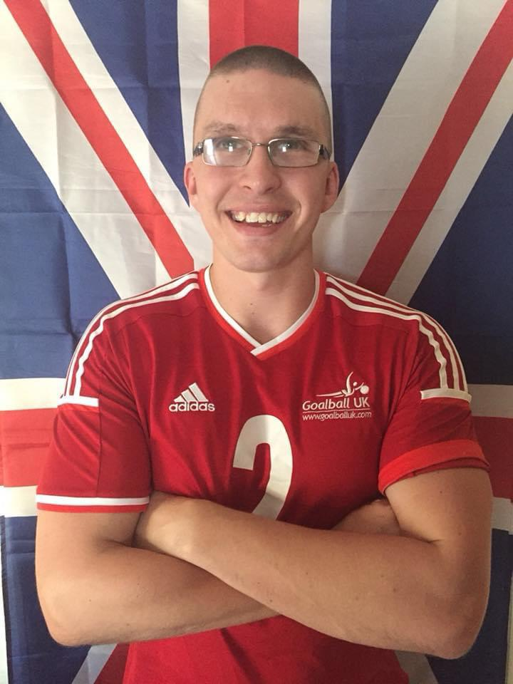 Image shows Matt Loftus stood smiling at the camera with his arms crossed wearing his GB Mens jersey