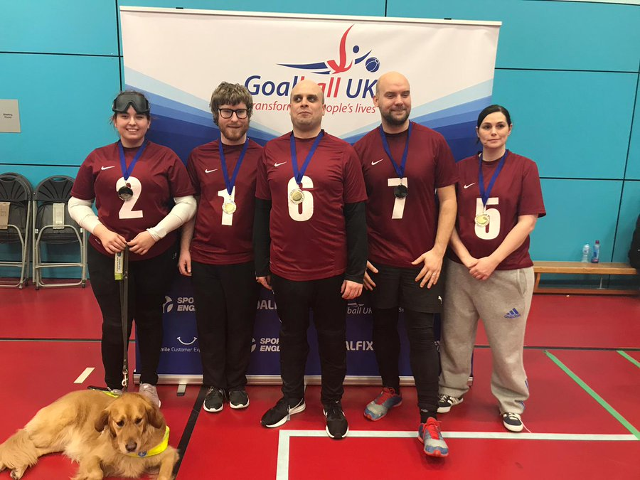 Image shows Gemma stood with her West Yorkshire teammates following a tournament. They are proudly wearing their medals in front of a Goalball UK banner.