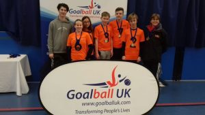 NCW team photo - players and coaches stood behind a Goalball UK banner with medals around their necks