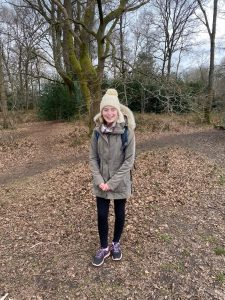 Phoebe stood in the woods wearing a big coat and a woolly hat