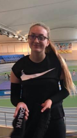 Image shows Samantha Gough stood at the EIS in Sheffield in front of the running track, holding her eye shades
