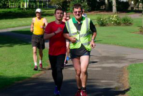 Anthony O'Keefe running at Hillsorough park run with his guide runner for the day