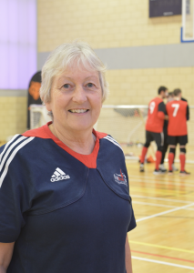 Image shows Judith stood wearing her Goalball UK t-shirt smiling at the camera