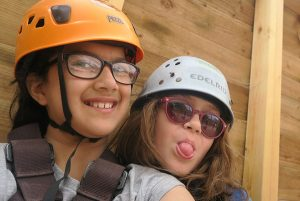 2 young girls with helmets and harnesses on, ready to take part in an outdoor activity