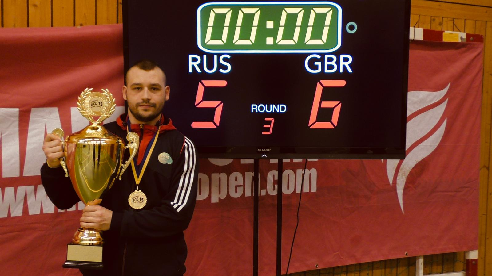 Image shows Dave Butler at the European Championships in front of a scoreboard, holding a trophy