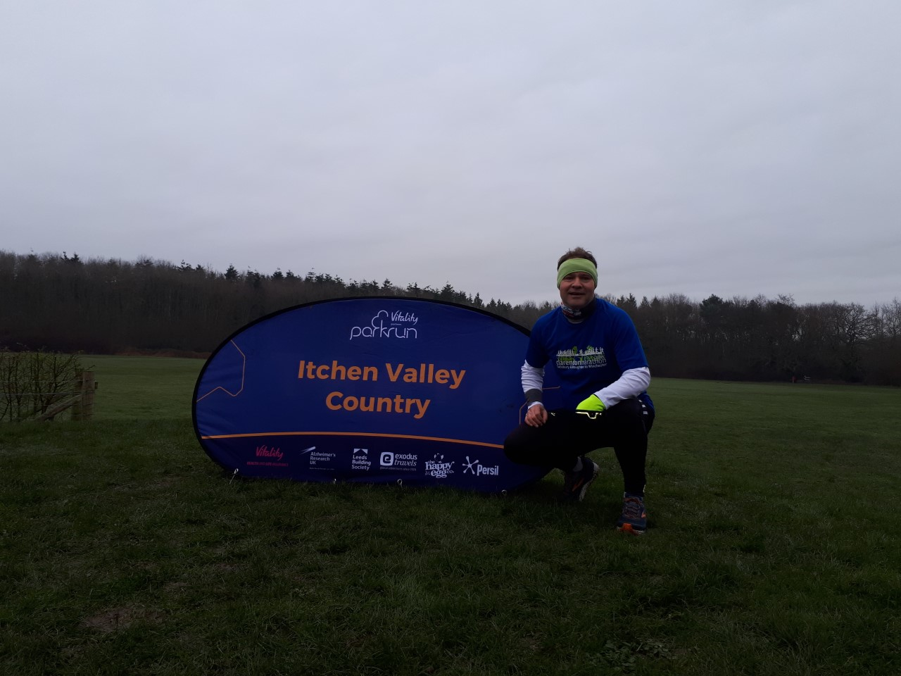Image shows Tom Evison squatting down next to an Itchen Valley Country banner following a Parkrun