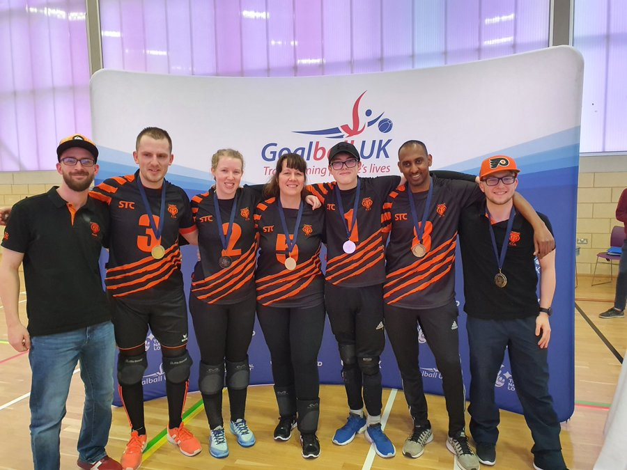 Image shows Georgie Bullen stood with her Fen Tigers teammates in front of a Goalball UK banner